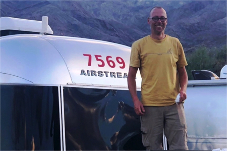 Man standing in front of airstream trailer
